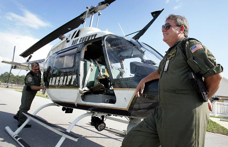 Dept. Chad Harrell, left, cleans oil off of the Bay County Sheriff's helicopter after patrolling the beach with his pilot, Sgt. Kenneth L. Smiley.
